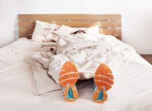 Woman sleeping in bed with running shoes on